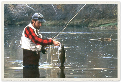 Angler, Tim Holschlag, standing in river with bass in hand
